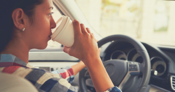woman driving with coffee